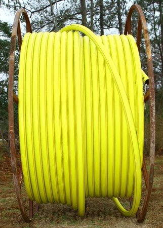 plastic conduit: A single large spool of yellow plastic conduit Stock Photo