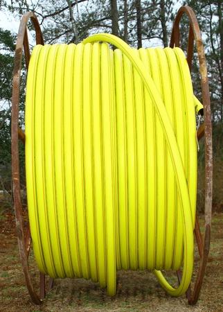 bury: A single large spool of yellow plastic conduit Stock Photo