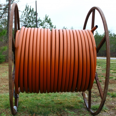 plastic conduit: A single large spool of brown plastic conduit Stock Photo