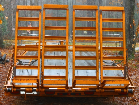 An old large orange wooden floor trailer with loading ramps for hauling tractors and equipment from place to place parked in the woods on a foggy day