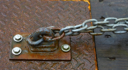 An old chain through an eyelet used as a hold down on diamond plate and wood Stock Photo