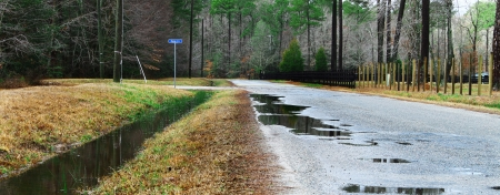 runoff: A ditch full of water runoff running along a road and fence in a rural neighborhood Stock Photo