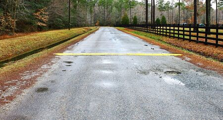 runoff: A ditch full of water runoff running along a road and fence with a speed bump and pothole in a rural neighborhood
