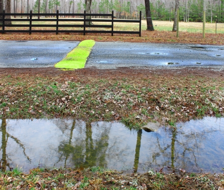 A ditch full of water runoff running along a road and fence with a speed bump and pothole in a rural neighborhood