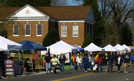 heralds: GLOUCESTER, VIRGINIA - APRIL 6: Main St vendors and pedestrians in the Daffodil Parade route on April 6, 2013 in Gloucester, Virginia. In its 27th year, the parade heralds the arrival of spring.