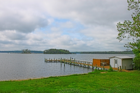 middlesex: An HDR of a fishing pierboat dock with a shed and cleaning station overlooking Berkley Island in the Piankitank river as seen from Middlesex Virginia Stock Photo