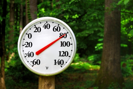 A thermometer on a pole reading the outdoor summer temperature using a shallow depth of field and selective focus with room for your text   Stock Photo