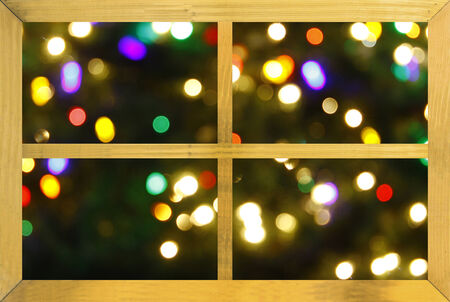 holiday celebrations: Looking at an abstract colorful christmas background through a wooden framed window