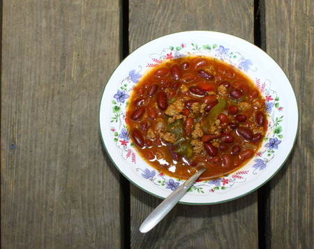 A bowl af fresh homemade Chili Beans on an old wirn and weathered wooden picnic table top with a spoon in them Stock Photo