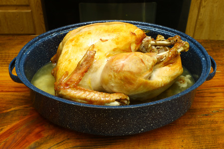 A fresh cooked Thanksgiving Turkey in a roasting pan on a wooden tabletop Stock Photo