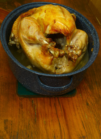A fresh cooked Thanksgiving Turkey in a roasting pan on a wooden tabletop 免版税图像