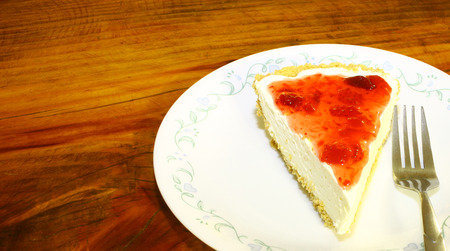 A fresh single slice of strawberry cheesecake on a ceramic plate with a fork on a wooden tabletop using a shallow depth of field