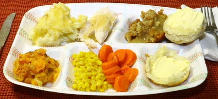 A traditional thanksgiving dinner served in a sectional styrafoam throw away plate on a wooden table