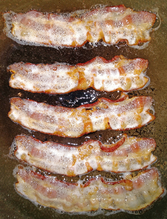 A frying pan with five strips of bacon frying in their own bacon grease on the stove top.
