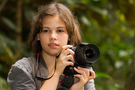 Beautiful girl holding a DSLR photo