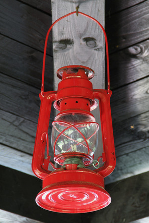 oil lamp: Vintage Red Lantern Hanging Under Roof  Red Oil Lamp Hanging Under Wooden Roof