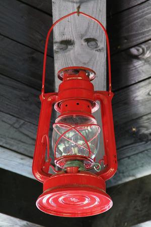 red oil lamp: Vintage Red Lantern Hanging Under Roof  Red Oil Lamp Hanging Under Wooden Roof