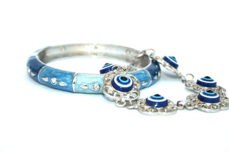 Metallic bracelet talisman with blue eyes and blue and cyan bracelet with silvery drops. photo