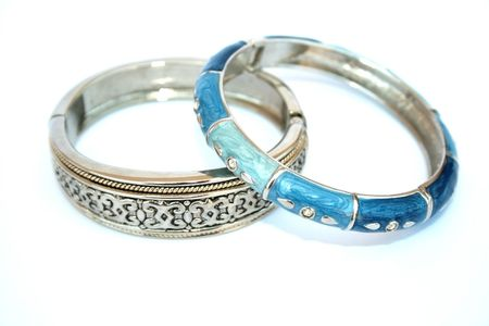 Silvery bracelet with ornament and blue and cyan bracelet with drops on the white. Stock Photo