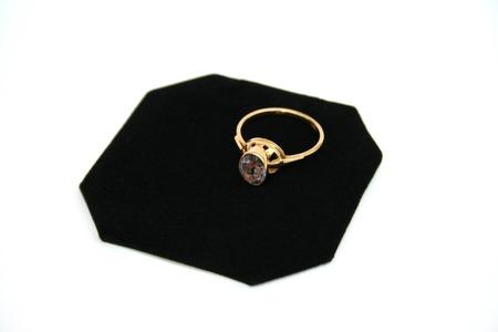 Golden ring with gemstone on black velvet. photo