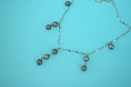 perls: Beautiful necklace with black perls isolated on the blue.