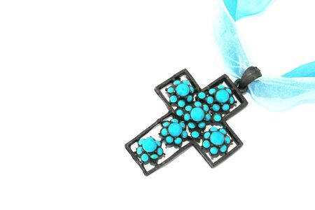Metallic cross with blue stones and ribbons on the white. photo