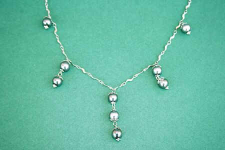 perls: Beautiful necklace with black perls isolated on the green. Stock Photo