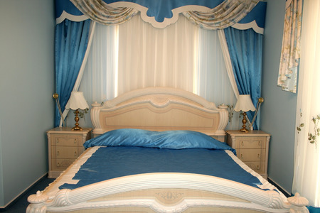 Nice blue bedroom with many luxurious details.