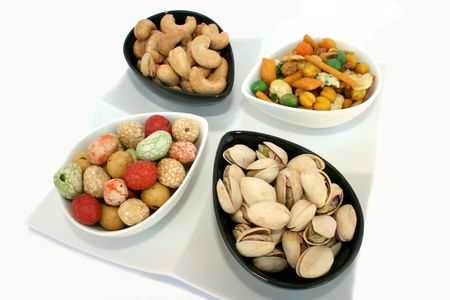 Different tasty nuts in the bowls on the white. photo