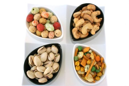 pista: Different tasty nuts in the bowls isolated on the white. Stock Photo