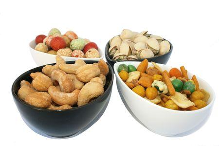 merienda: Diferentes y sabrosos frutos secos salados en los cuencos aisladas en el blanco.