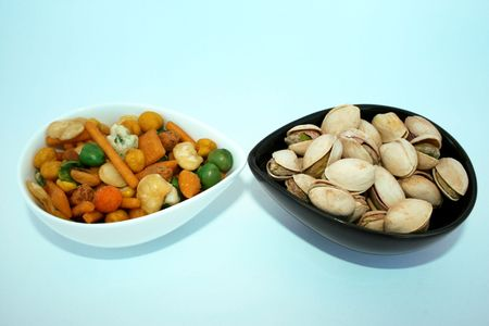 pista: Different tasty salted nuts in the bowls.Isolated. Stock Photo