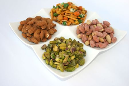 pista: Different tasty nuts on the dish.Isolated.