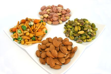 pista: Different nuts on the dish isolated on the white.