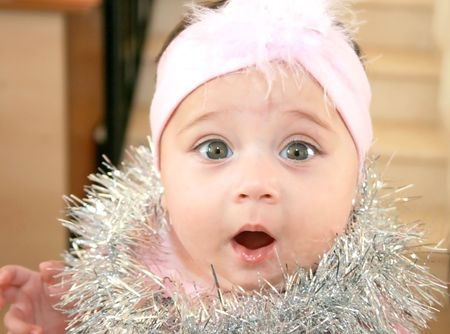 december: Christmas baby girl in pink with christmas ornament.