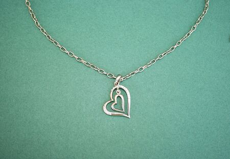 Two hearts with stones and necklace isolated on the green. photo