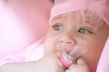 Pretty baby girl in pink with dummy. Stock Photo - 2940919