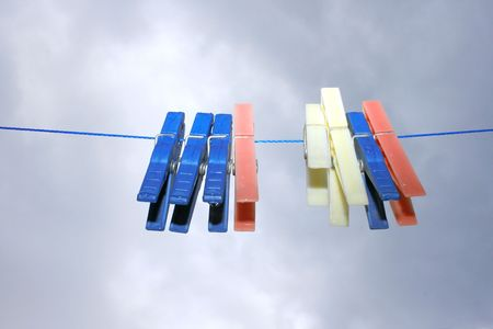 Colorful clothespins with rain drops on the rope on the sky background. photo
