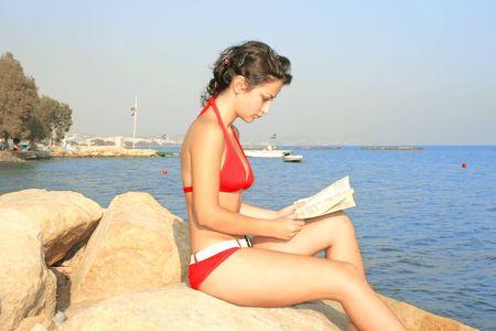 Pretty girl in red bikini with book on the beach. photo