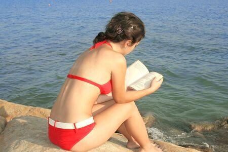 Pretty girl reading book on the beach. photo