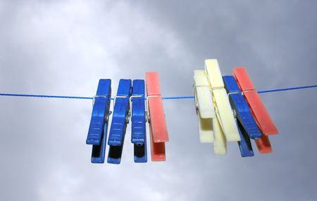 Colorful clothespins with rain drops hanging on the rope on the sky background. photo