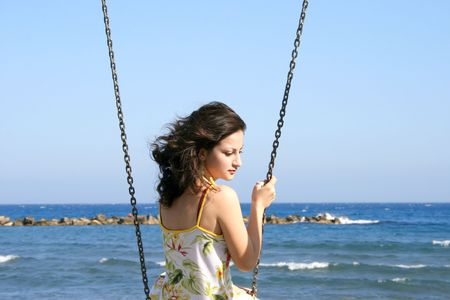 Pretty girl above the sea holding the chain.