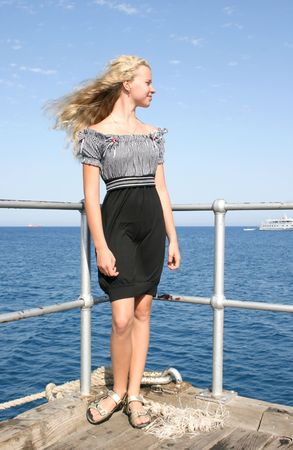 Pretty blond girl on the pier at the sea. photo