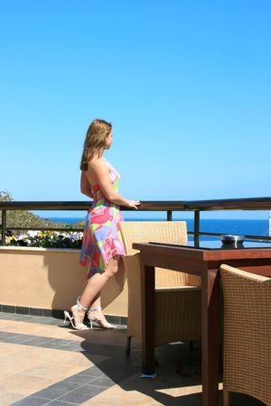 Pretty blond girl on the balcony watching the sea. photo