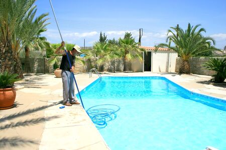 maintenance man: Swimming pool cleaner during his work.