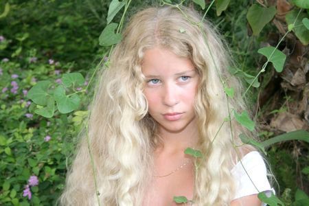 Pretty blond mermaid with green leaves. photo