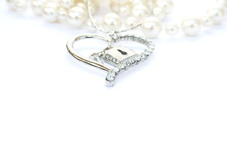 Silver heart with key,lock,pearls on white background.