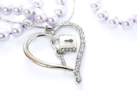 Silver heart with key,lock,pink pearls on white background. photo