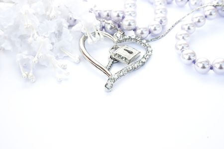 Silver heart with key,lock,pearls and flowers on white background.