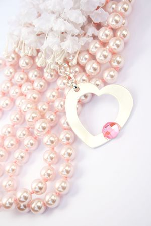 Necklace with heart medallion with pink stone on it, pink pearlsand white fabric flowers.. Stock Photo - 4156760
